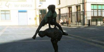 """Estatua de niños jugando frente al tren """"topo"""" de Rentería"""